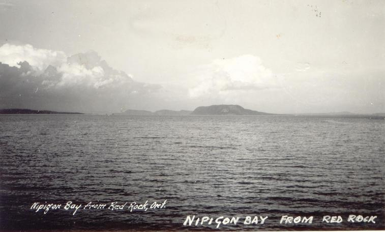 [caption on back]  The picture is taken from our camp which is on the West side of the lake.  The Land which you see in the centre of the picture is an island & if you were in a boat & kept bearing around to the right for about 100 miles it would take you to Port Arthur & Fort William.